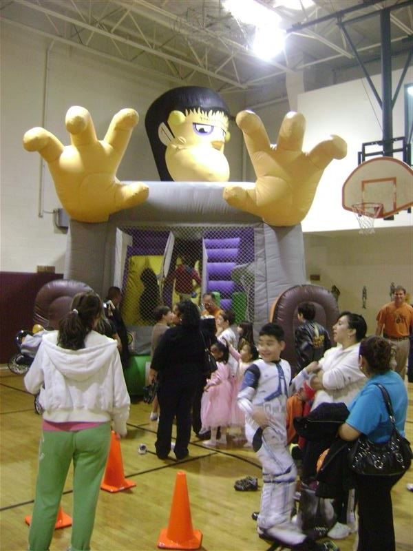 Children standing outside of a Frankenstein-themed bouncy house.