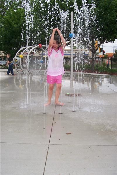 A little girl playing in sprinklers.