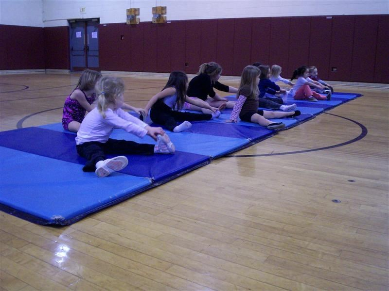 People gathered on a mat, doing yoga.