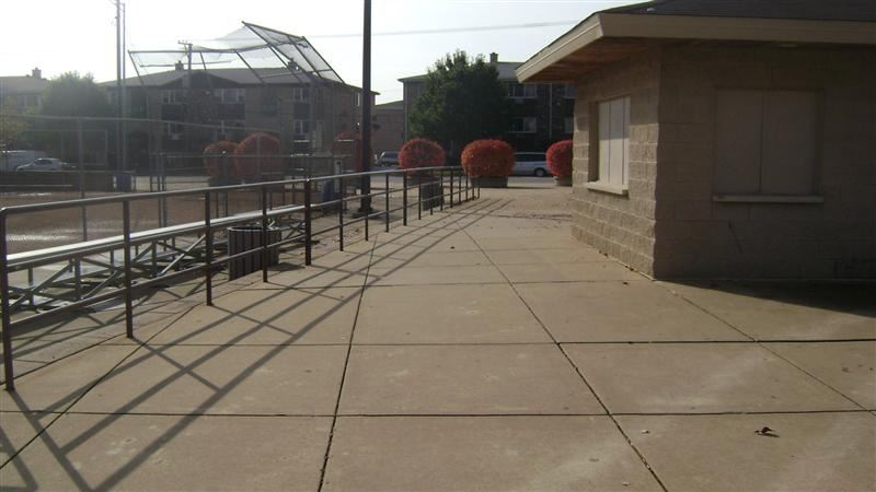 A paved pathway next to a tan building.