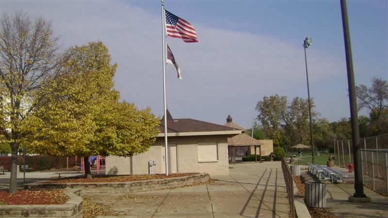 An American flag waving over a tan building.
