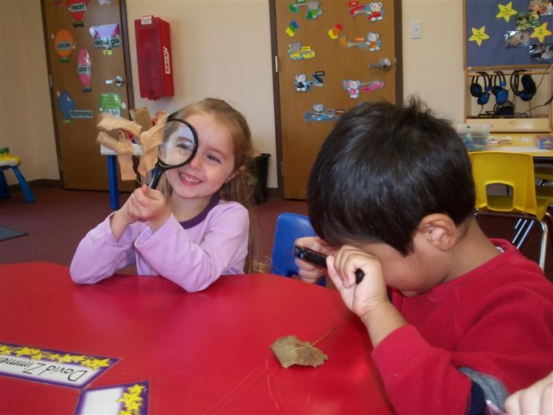 A boy and girl playing with magnifying glasses.