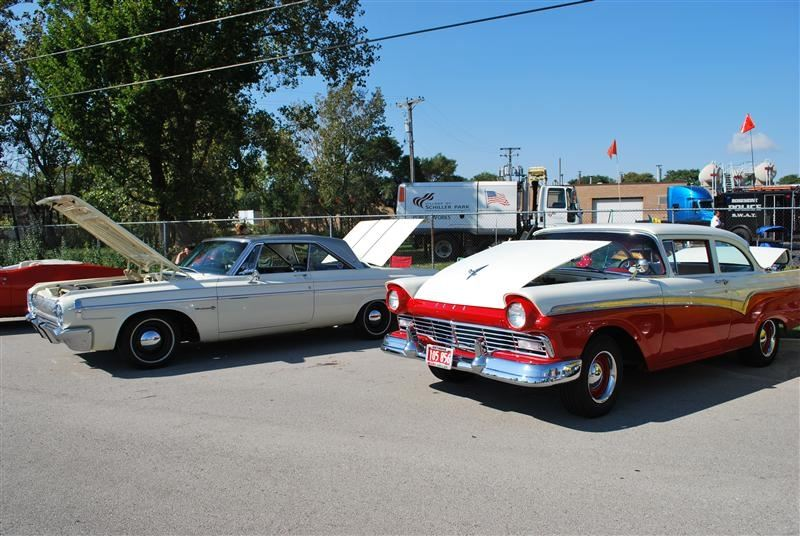 A vintage red car and a vintage white car.