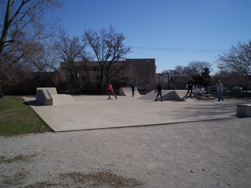 Youths skateboarding on a large concrete park.