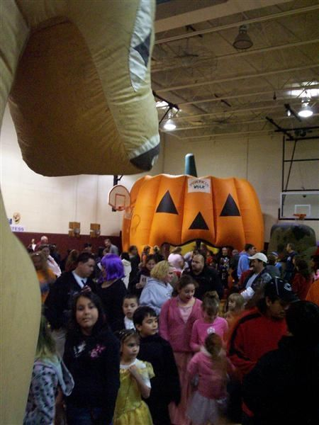 A crowded gymnasium with a large inflatable pumpkin.