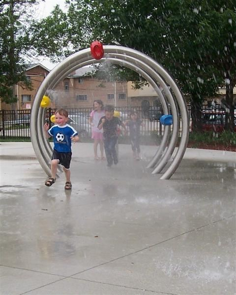 A little boy walking through a water sprinkler.