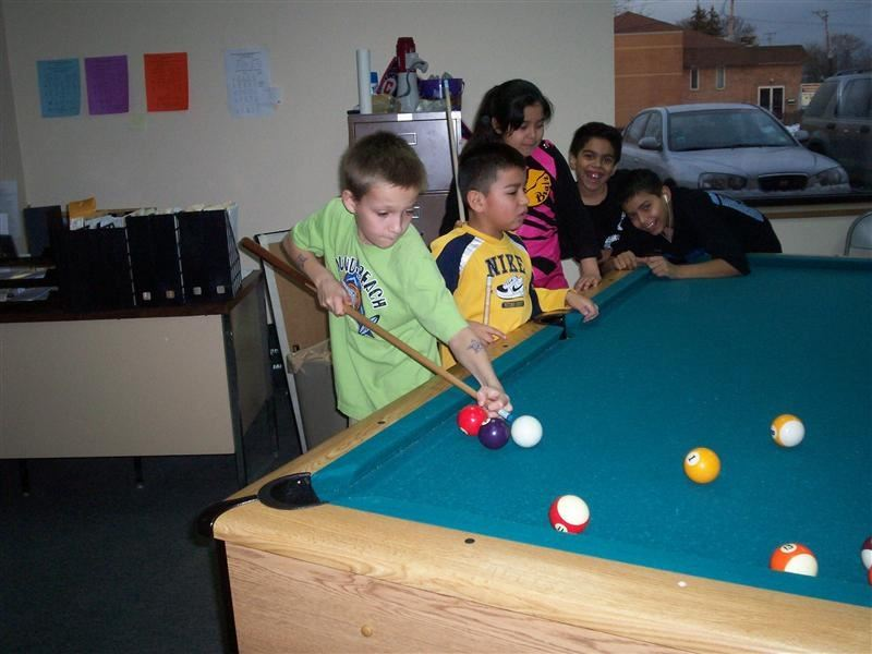 Young children playing billiards.