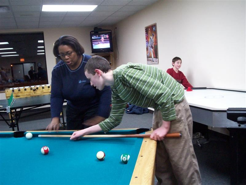 A group of people playing billiards.