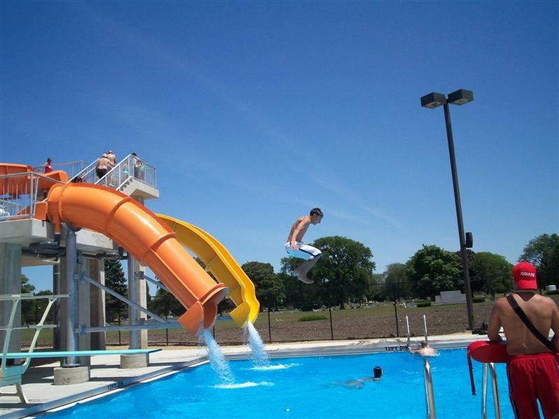 People sliding down an orange waterslide into a pool.