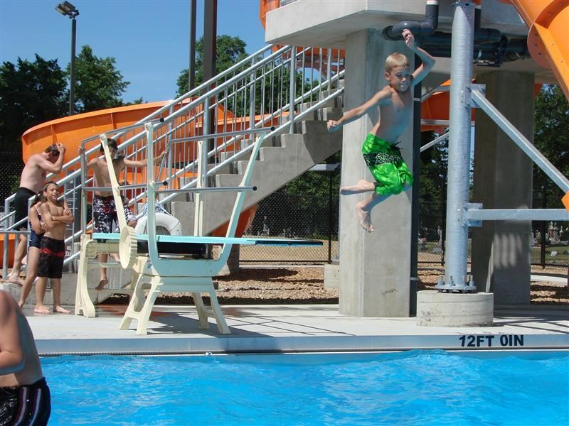 A boy jumping off of a diving board.